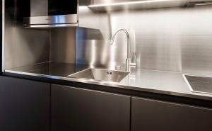 Contraste entre la cuisine en Fenix noire et le plan de travail en inox avec évier intégré.